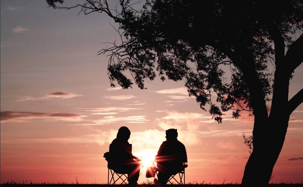 two people watching the setting sun sitting on chairs