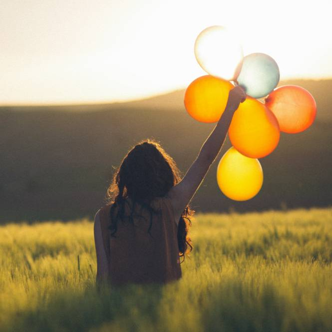 Happy woman holding balloons
