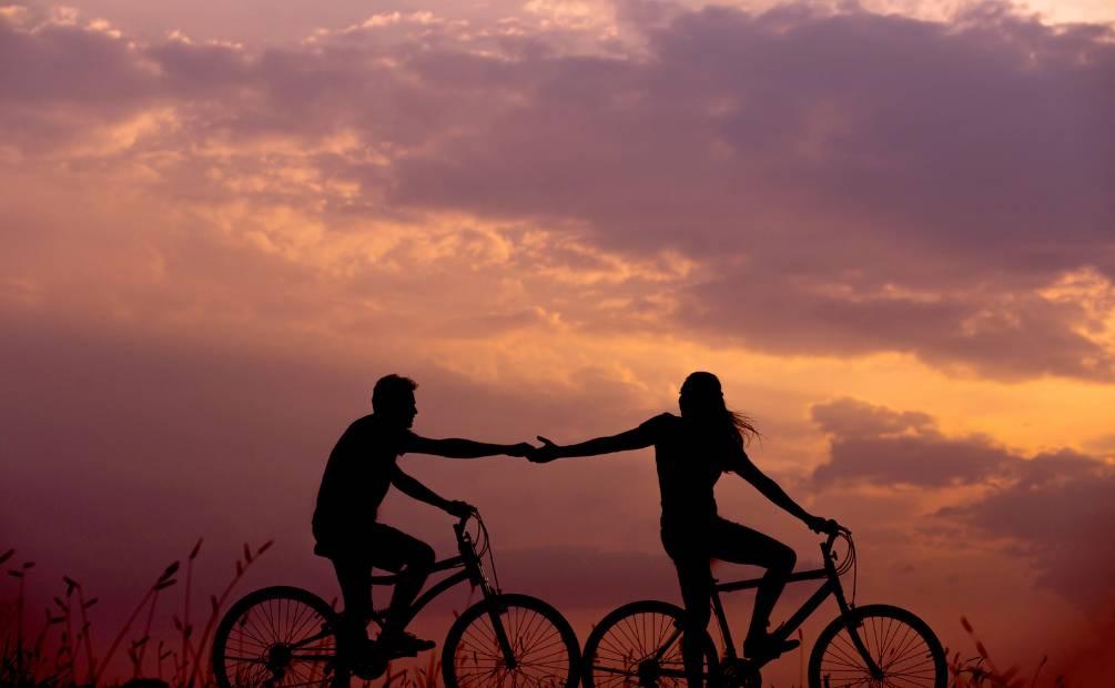 Deux personnes sur un vélo qui s'entraident