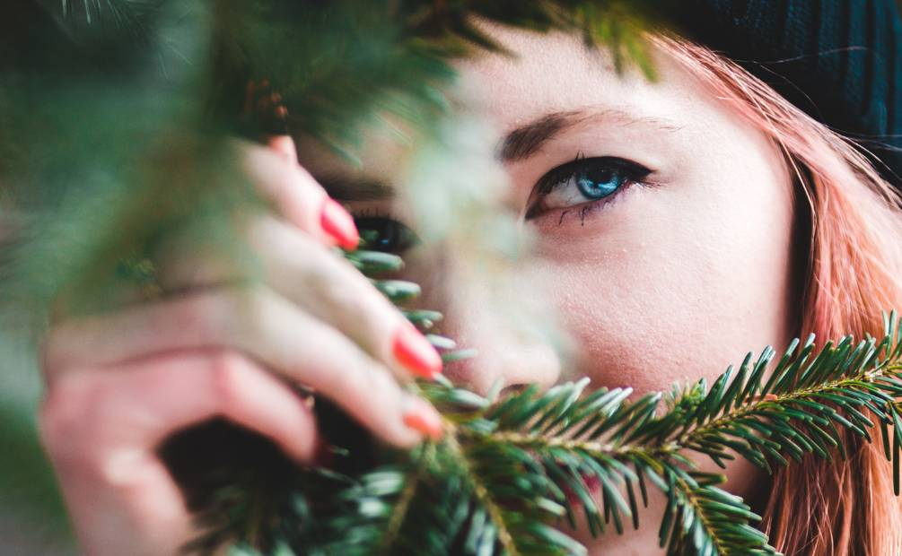 Woman looking through the branches of a tree