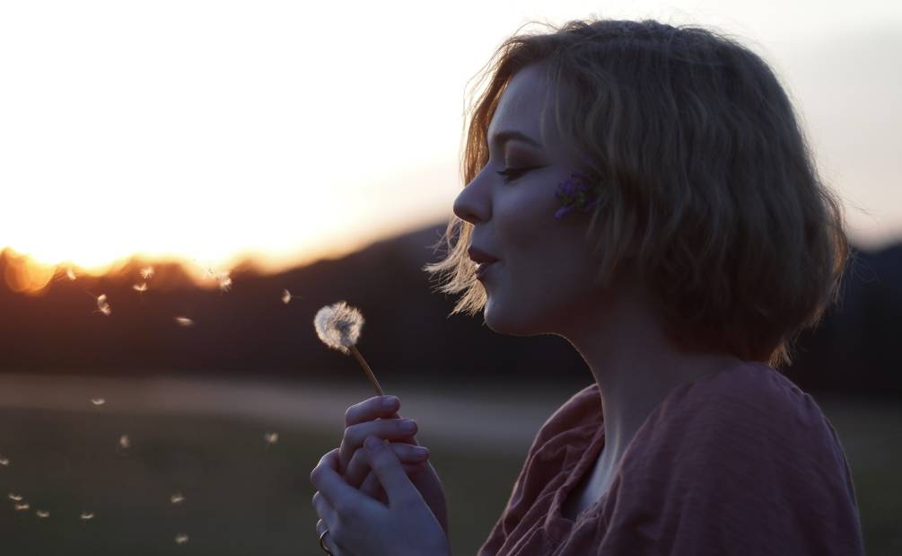 a women blowing on a dandelion