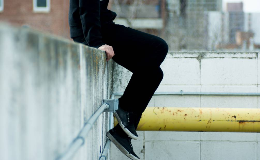 legs of a teenager sitting on a wall