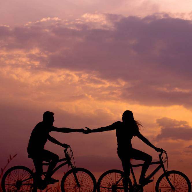 2 people on bikes helping each other