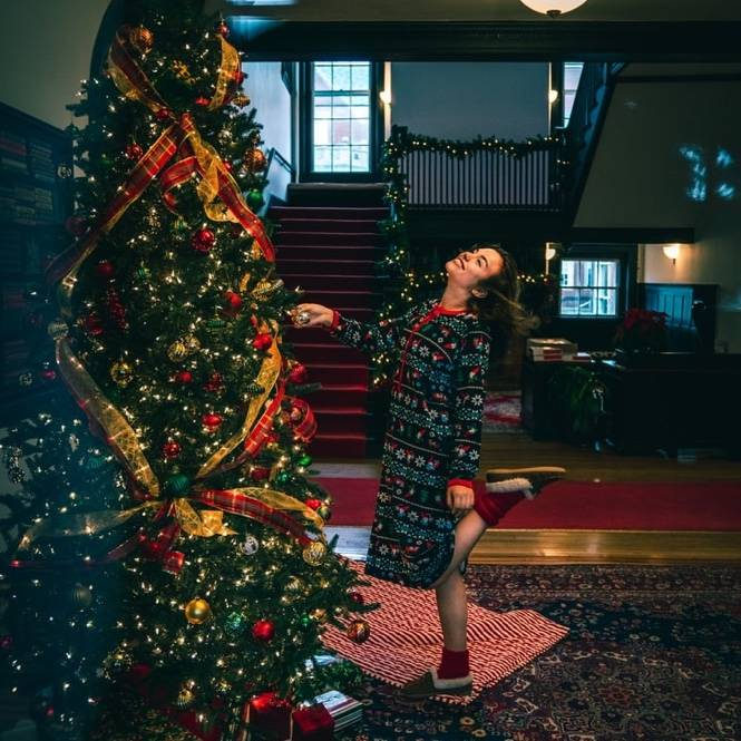 woman happy next to her christmas tree