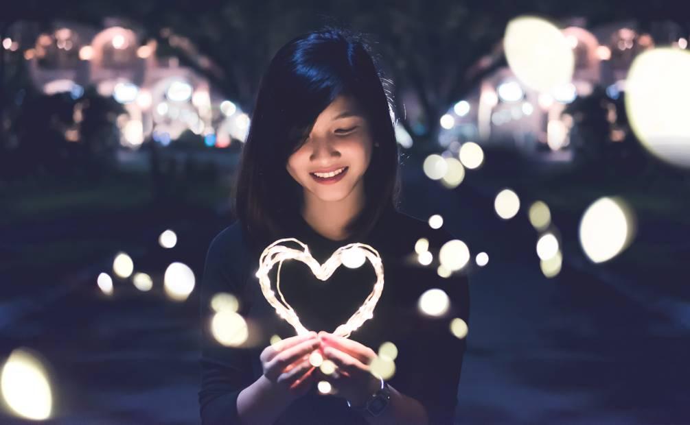 Femme tenant une guirlande en forme de coeur