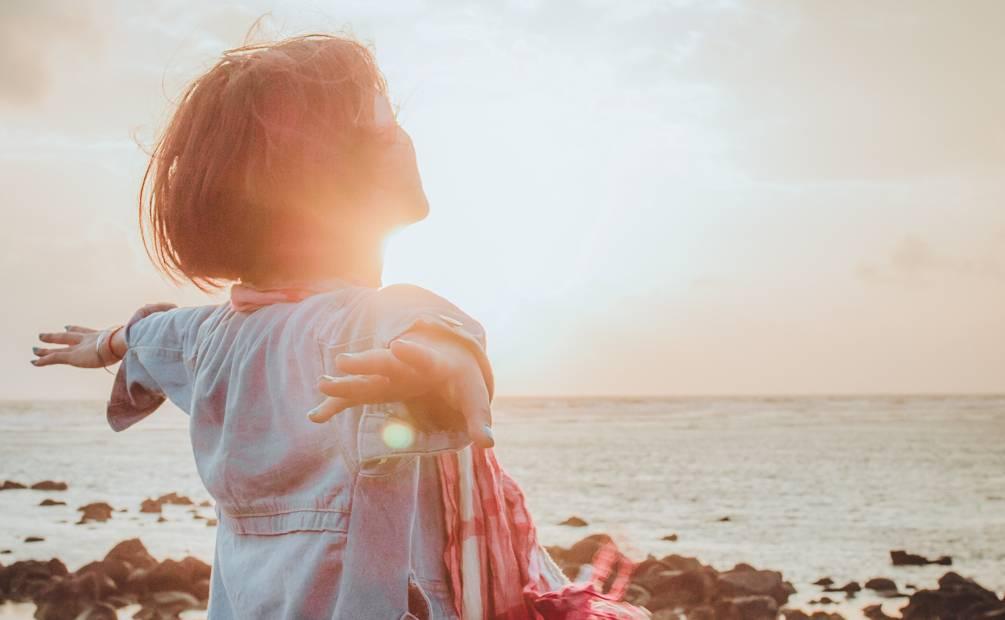 femme respirant face à la mer