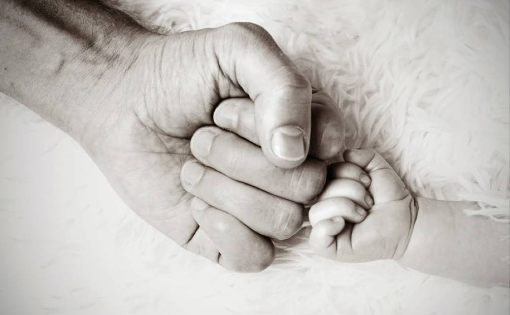 homme qui tient la main d'un enfant