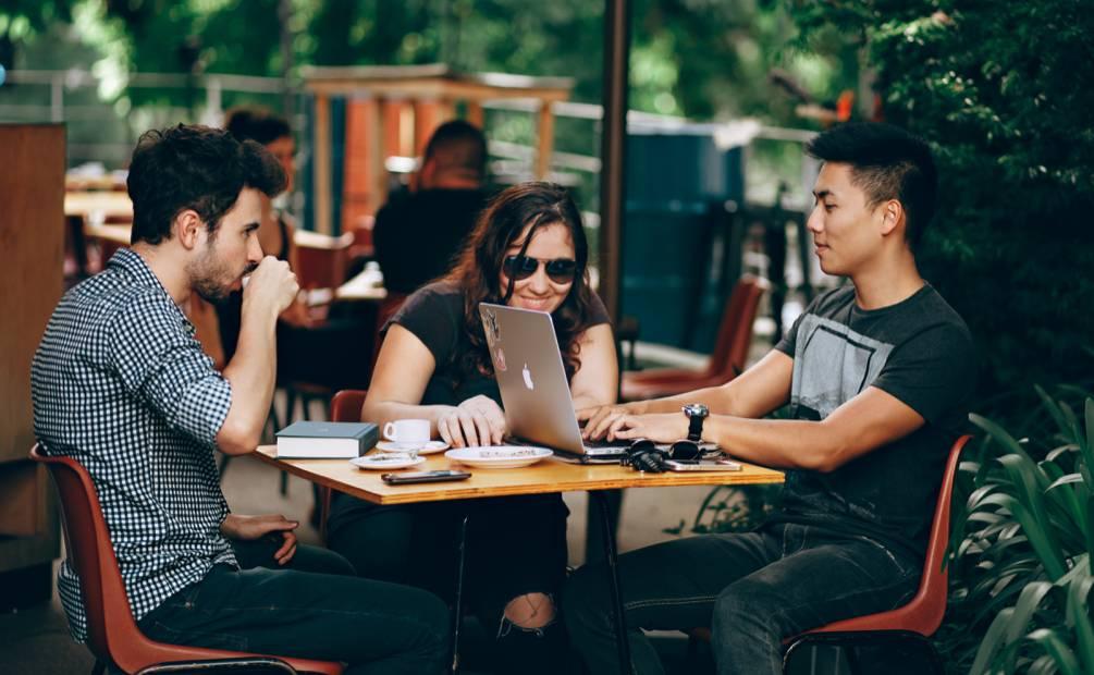 trois collègues travaillant en terrasse