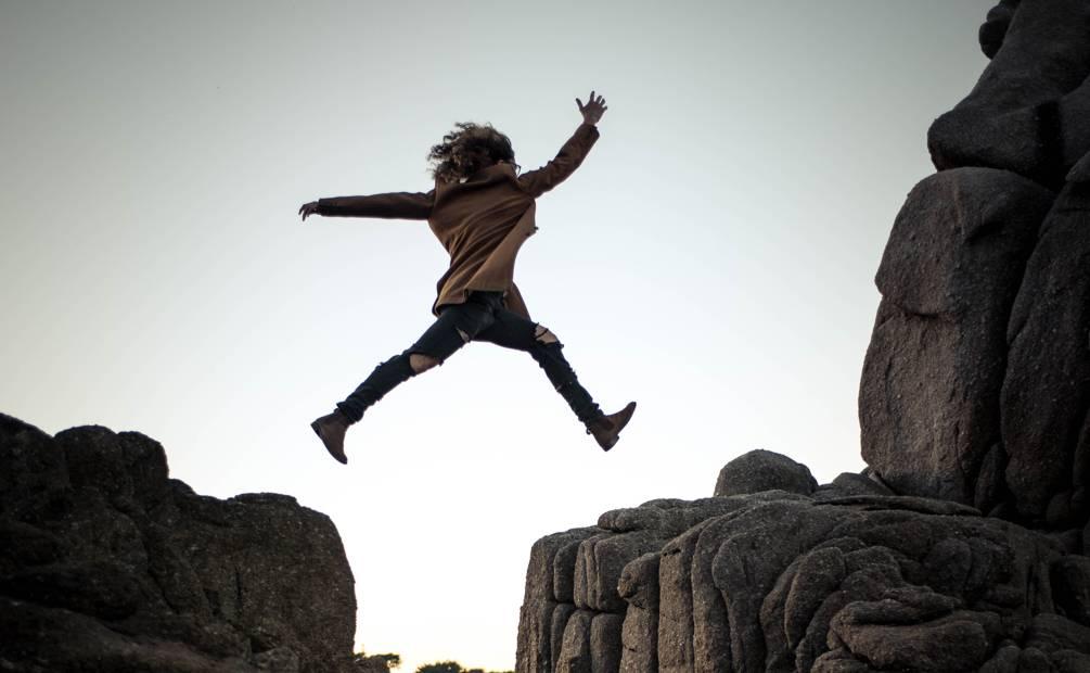 femme qui saute pour éviter un vide entre deux falaises