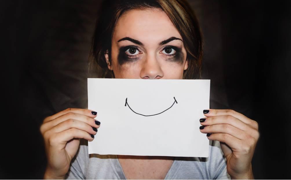 femme qui tient un sourire dessiné sur un papier devant sa bouche.