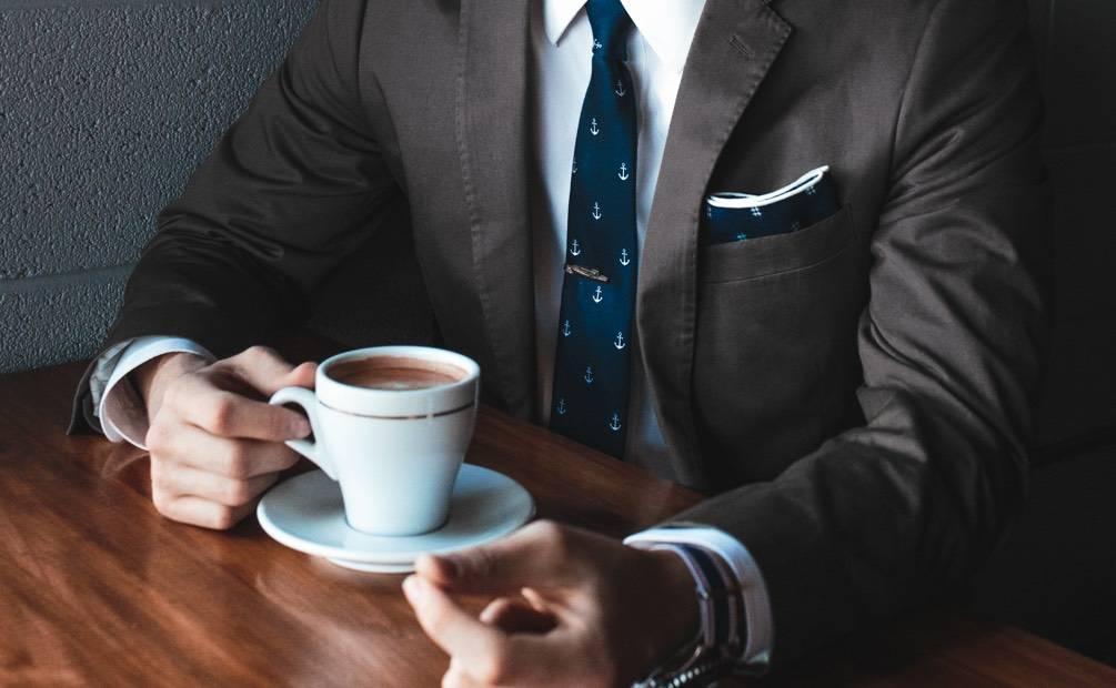 femme en costume tenant café