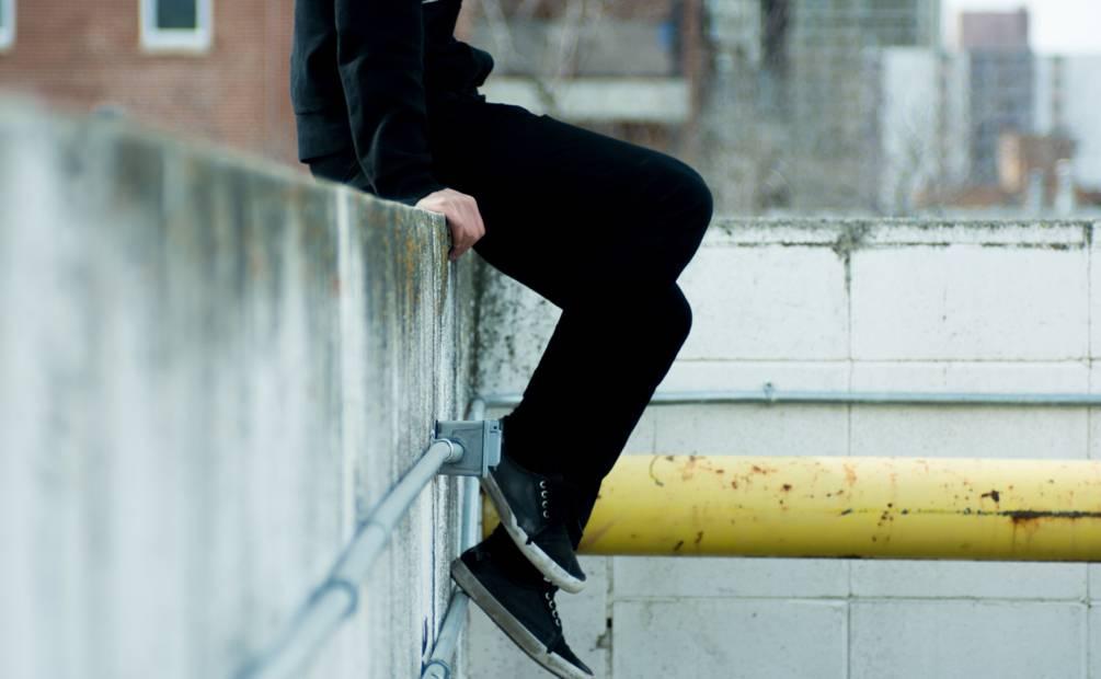 jambes d'un adolescent assis sur un mur