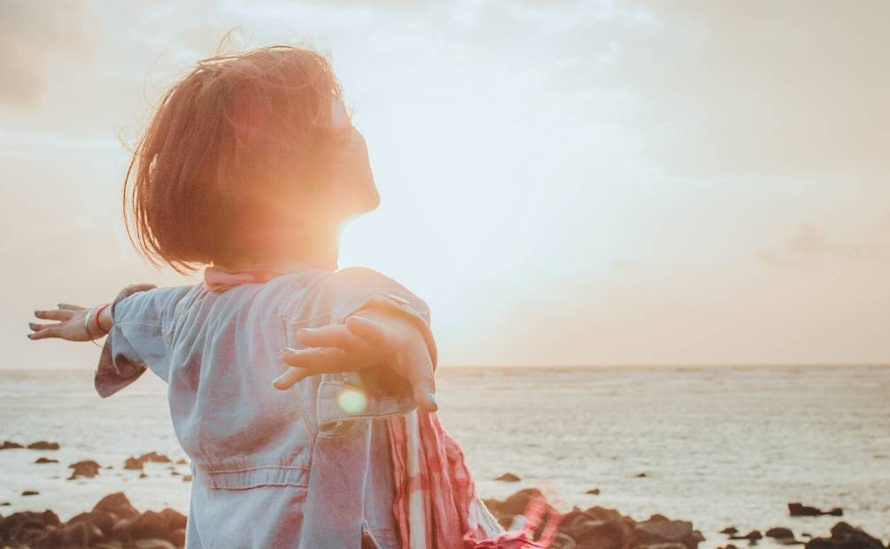 Woman opening her arms wide in front of the sunrise
